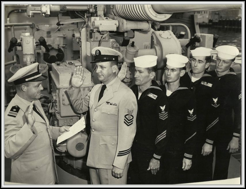photograph of Captain Raymond E. Davis administering the Enlistment Oath to 5 unknown Savage shipmates.