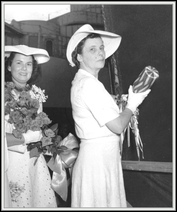 photograph of Mrs. Savage holding champagne bottle before christening