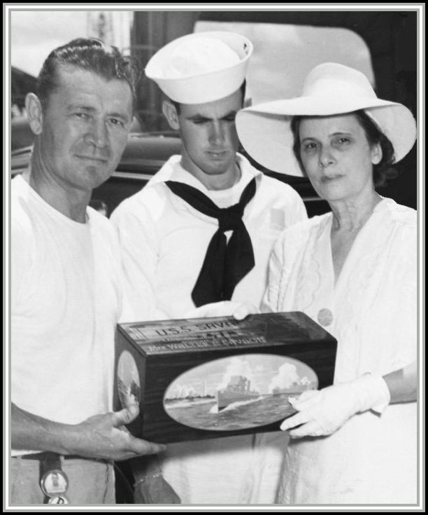 photograph of ship's foreman presenting Mrs. Savage with sea chest containing broken champagne bottle.  John Savage looks on in middle.