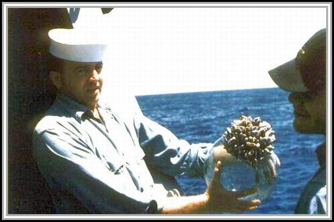 photograph of sailor holding fishing ball covered with barnacles