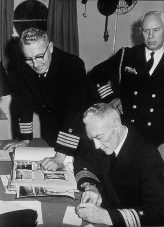 photograph of Captain O. C. Rohnke looking on as Admiral Richard E. Byrd writes a note to Karl E. Rohnke inviting him to join them on Operation Deepfreeze.  Other officer pictured is unidentified.  Circa 1955.